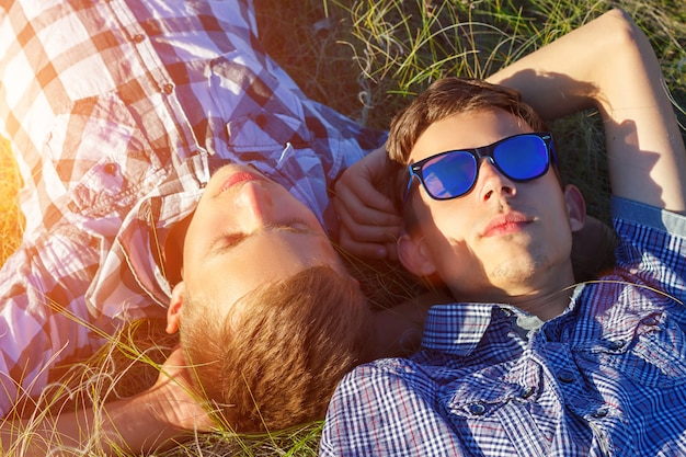 Двое друзей лежат на траве