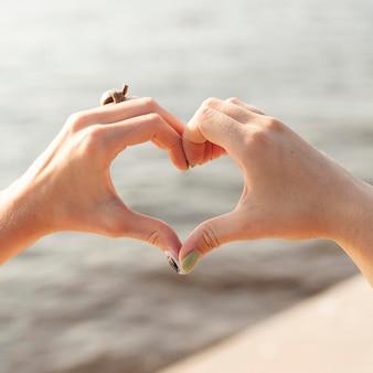 Двое друзей делают знак сердца на озере руками