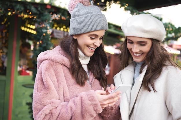 携帯電話を閲覧しているクリスマスマーケットの2人の友人