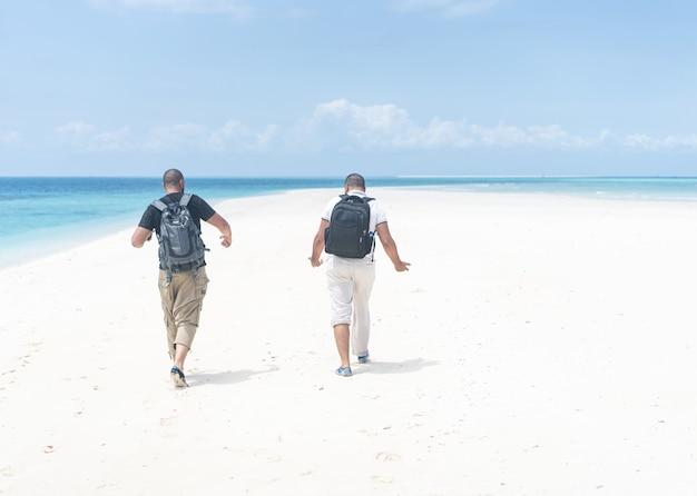 Двое друзей на красивом горячем пляже