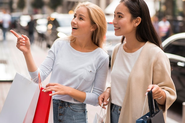 店を指さしている買い物に出かける2人の友人