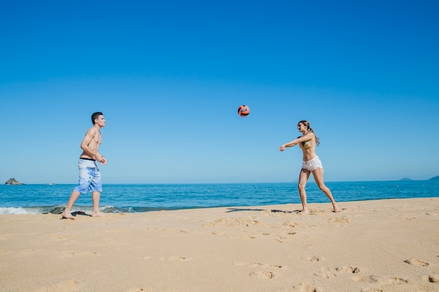 Two friends playing beach volleyball Free Photo