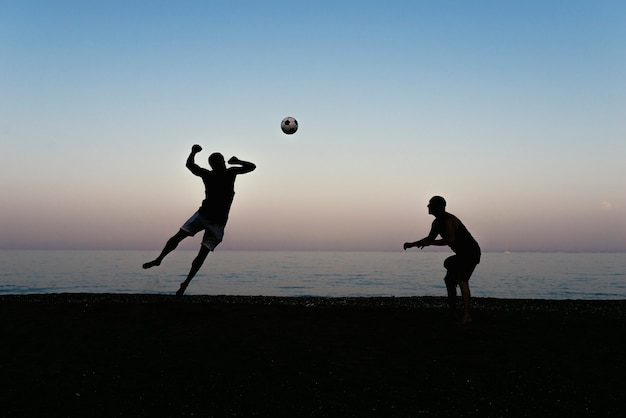 Two friends playing soccer in the beach.