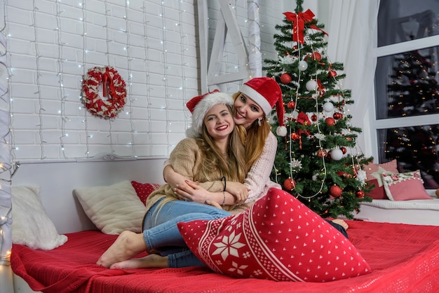 ベッドに座って新年のスタジオでポーズをとる2人の友人