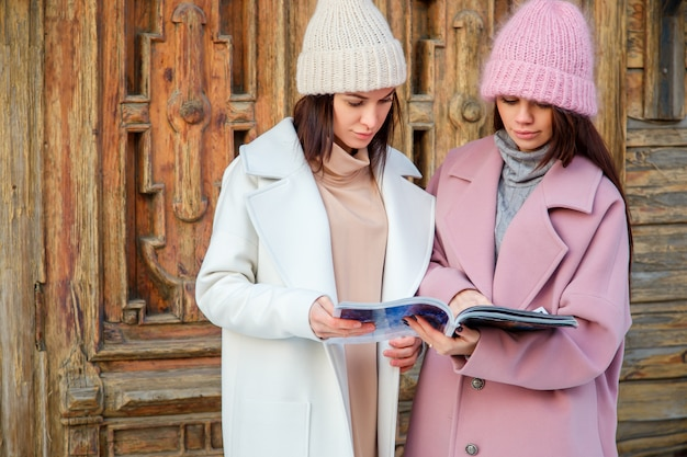 Two friends reading a magazine together