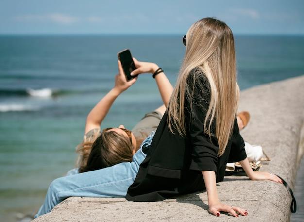 Двое друзей отдыхают и со смартфоном