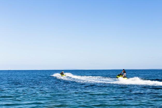 イビサ島でスクーターに乗って2人の友人。夕暮れ時の青い海。楽しさと休日のコンセプト