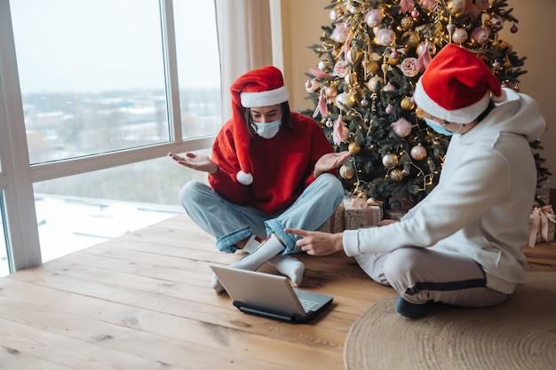 Due amici in cappello della santa vicino al laptop stanno interagendo tramite videochiamate. natale in isolamento a casa. allontanamento sociale per le vacanze.