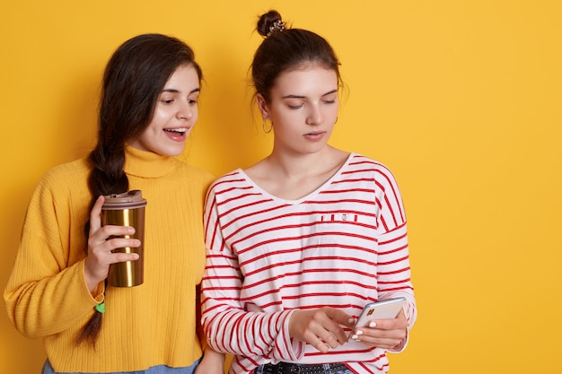 Two friends sharing smart phone and drinking coffee together, posing
