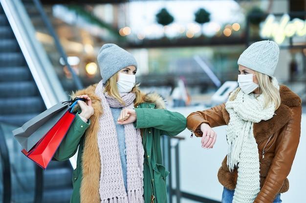 마스크, 코로나 바이러스 개념을 입고 함께 쇼핑하는 두 친구