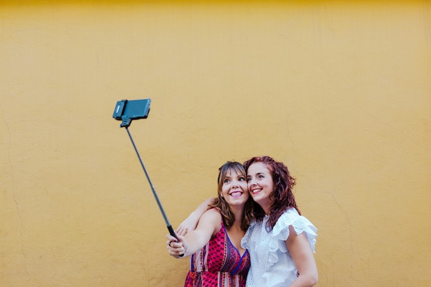 Two friends or sisters taking a selfie outdoor