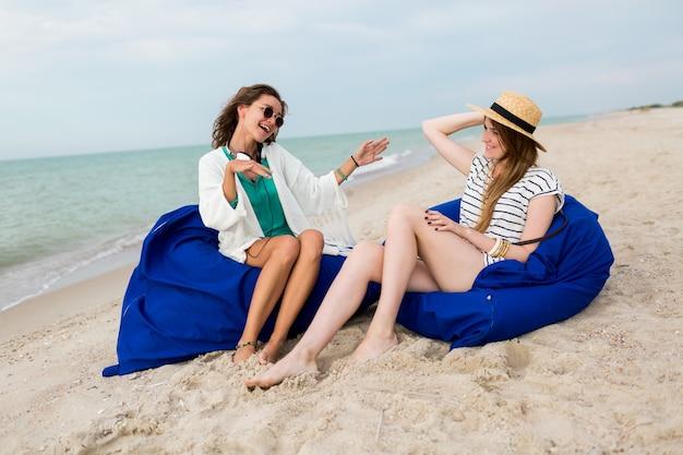 Двое друзей сидят на пляжных подушках, веселятся