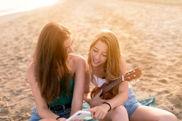 Two friends sitting on beach looking at mobile phone