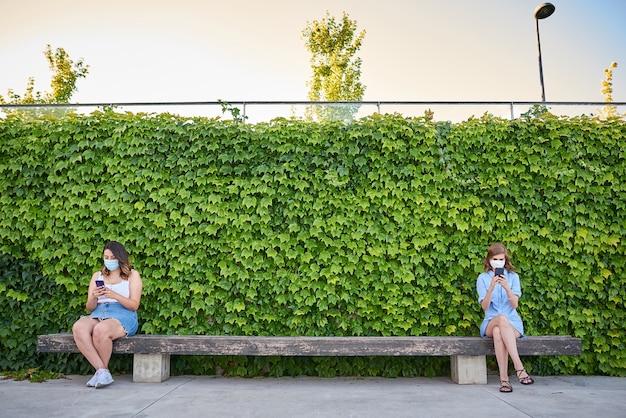 바이러스 마스크를 쓰고 공원에 앉아있는 두 친구가 전화를 들고 있습니다.