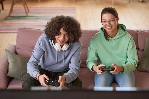 ソファに座って、自宅でオンラインビデオゲームで一緒に遊んでいる2人の友人