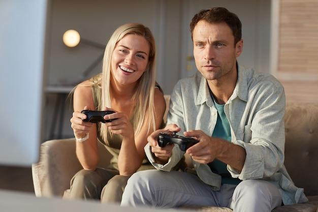 コンピュータゲームで遊んでいるソファに座って、一緒に余暇を楽しんでいる笑顔の2人の友人
