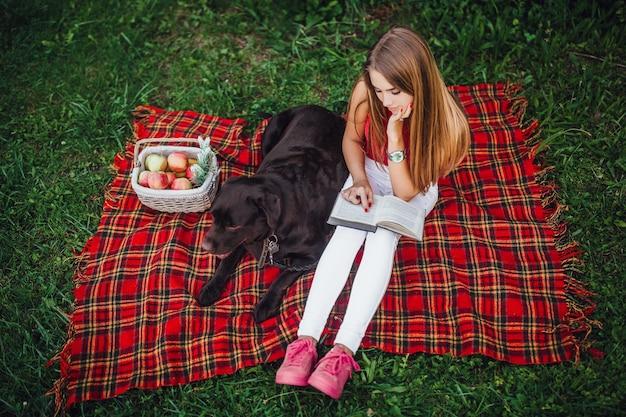 公園で切り刻まれた毛布の上に座っている2人の友人