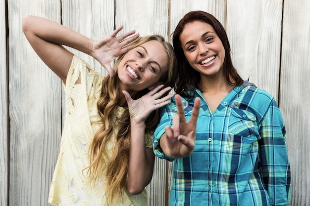 Two friends smiling at camera making gesture