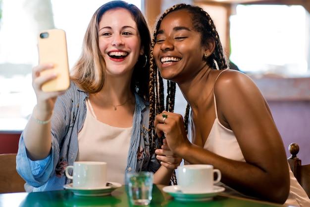コーヒーショップでコーヒーを飲みながら携帯電話で自分撮りをしている2人の友人。友達のコンセプト。