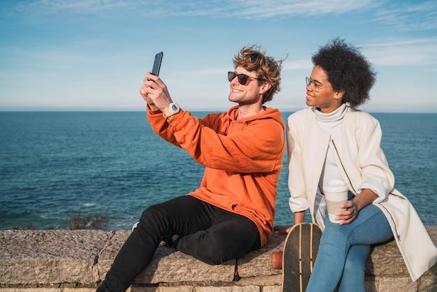 Smartpone와 함께 selfie를 복용하는 두 친구.
