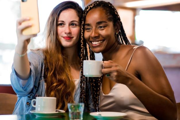 Due amici che si fanno un selfie con il cellulare mentre bevono una tazza di caffè in una caffetteria. concetto di amici.