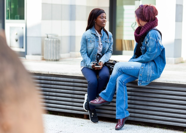 Two friends talk sitting on a bench.