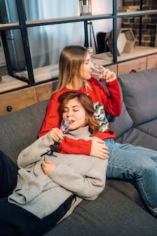Двое друзей разговаривают, сидя на диване в гостиной