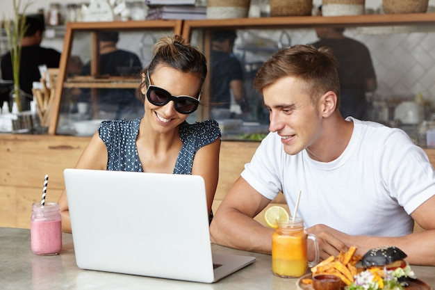 Two friends using laptop pc together during meeting at coffee shop, sitting at table with food and drinks in front of generic notebook computer, looking at screen and smiling