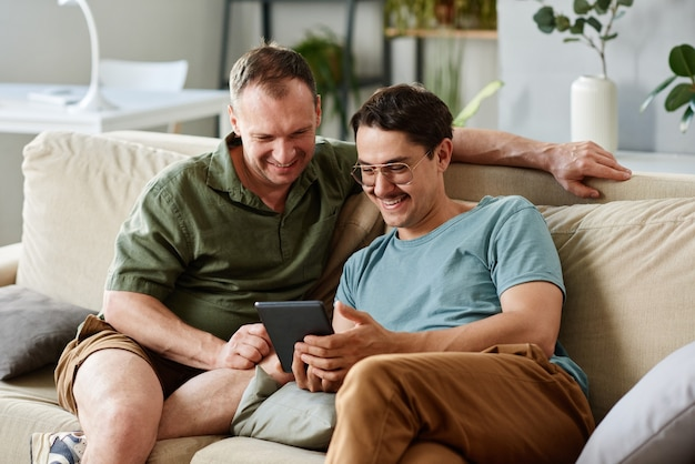 Двое друзей вместе используют планшетный пк, сидя на диване в комнате дома