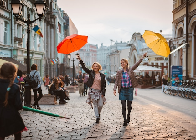 Two friends walk in the city center under bright umbrellas in the autumn or spring season