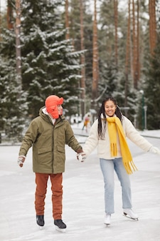 Two friends in warm clothing holding hands and skating together in winter day