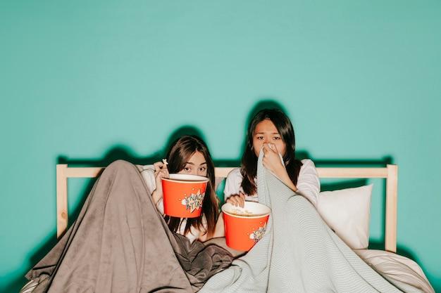 ポップコーンで怖い映画を見ている2人の友人