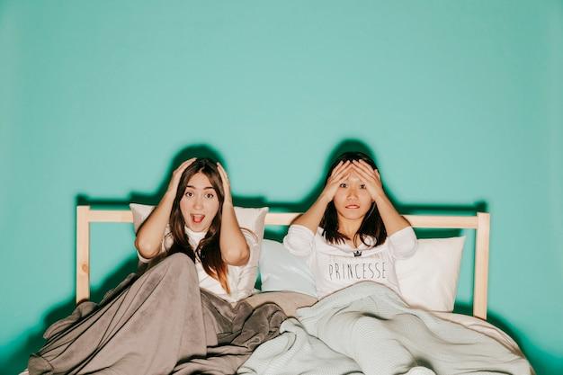 ベッドでスリリングな映画を見ている2人の友人