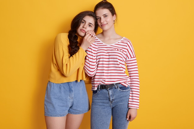 Two friends wearing stylish clothing standing isolated over yellow wall