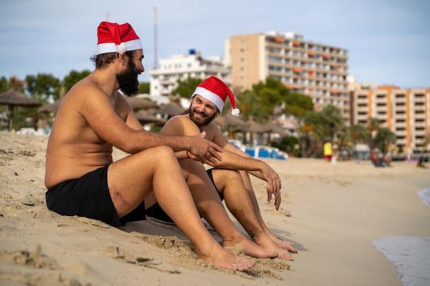 Два друга в шляпе санта-клауса разговаривают на пляже пальманова, улыбаются, веселятся и пользуются солнечной погодой зимой