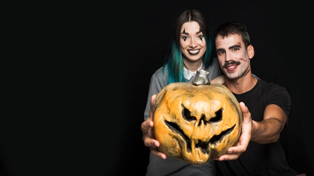 Two friends with creepy makeup with jack-o-lantern