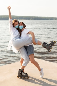 Two friends with face masks and roller blades having fun by the lake