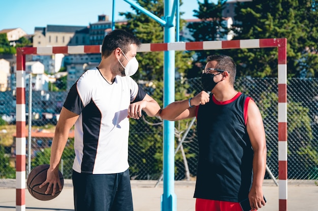 Two friends with masks greet each other before starting to play basketball