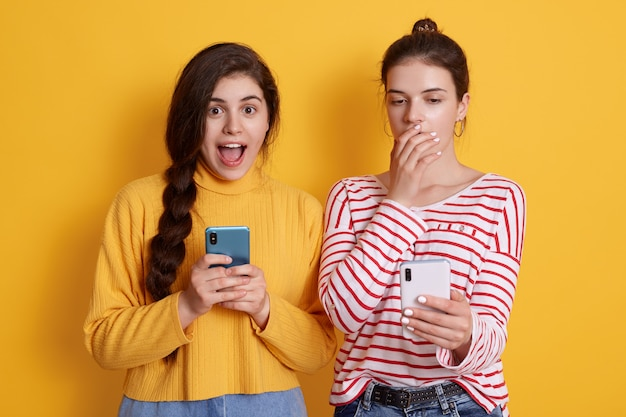 Two friends with phones reading shocking news in social network