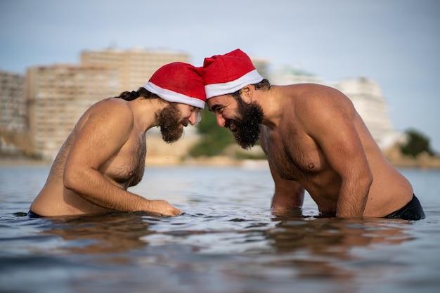 Два друга в шляпе санта-клауса стоят друг против друга на пляже