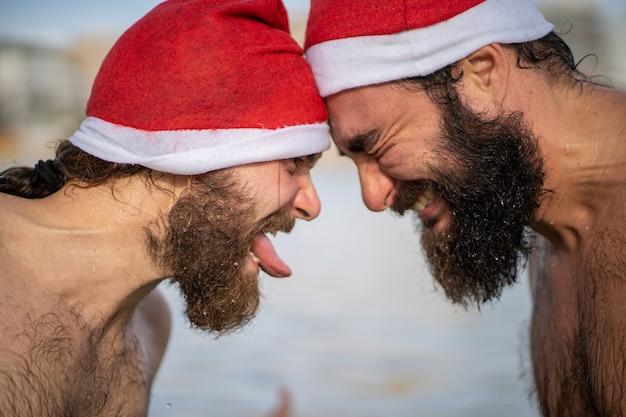 Два друга в шляпе санта-клауса стоят друг против друга на пляже два друга в шляпе санта-клауса стоят друг против друга на пляже на майорке