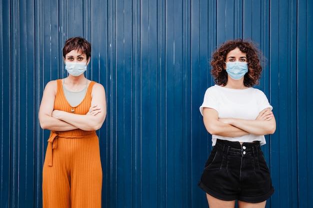 팔짱을 끼고 서 있는 얼굴 마스크를 쓰고 야외에 있는 두 명의 친구 여성. 사회적 거리 개념입니다. 코로나 바이러스 동안 전염병.