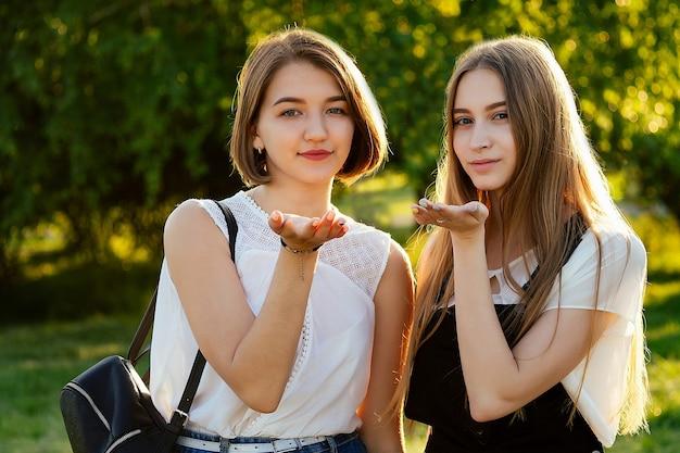 Две лучшие подруги дружбы студентки послали воздушный поцелуй в парке