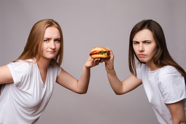카메라를 보고 식욕을 돋 우는 해로운 햄버거를 들고 두 찡그린 젊은 아름 다운 여자. 회색 스튜디오 배경 중간 샷에서 격리된 건강에 해로운 패스트푸드와 함께 포즈를 취하는 유럽 여성을 승인하지 않음