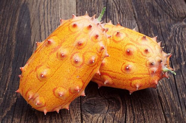 두 과일 kiwano - 오래된 나무 테이블에 아프리카 뿔 멜론 또는 오이