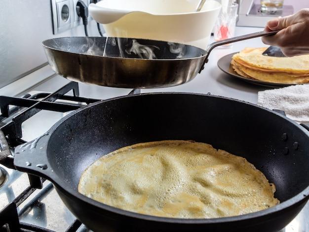 Две сковороды на газовой плите, в которых пекутся ароматные вкусные блины домашняя кухня