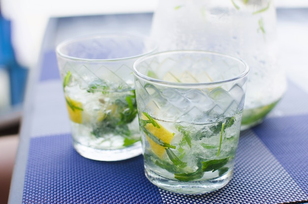 Two full glasses of fresh cool transparent water with ice, lemon and , basil leaves