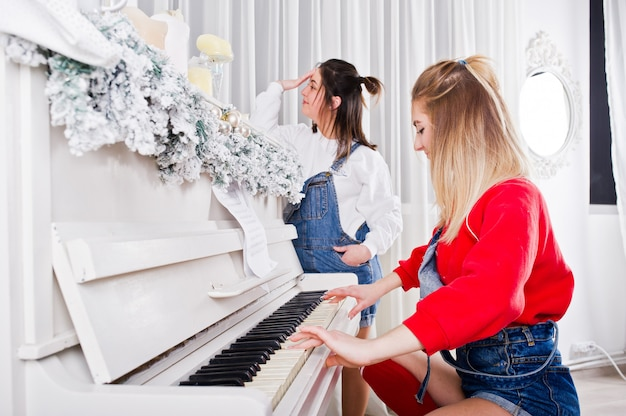 Two fun beautiful girls friends wear in overalls jeans shorts and gaiters against piano