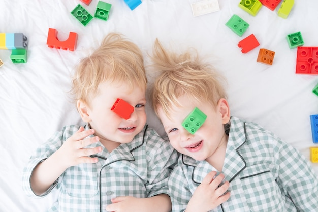 Two funny boys brothers twins lying on white bed in pajamas with colorful constructor.