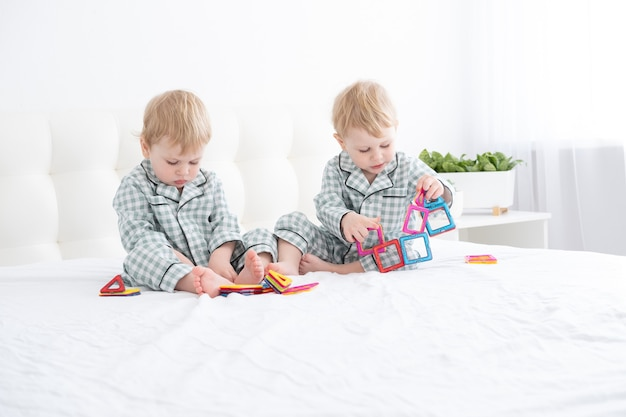 Two funny boys brothers twins on white bed in pajamas playing in magnetic constructor